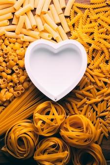 Tafel vol met verschillende soorten pasta met een hartvorm in het midden, pasta lovers