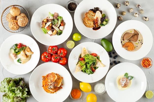 Tafel vol voedsel bovenaanzicht op betonnen tafel. set gerechten op tafel. vleessalade en dessert op tafelbladweergave.