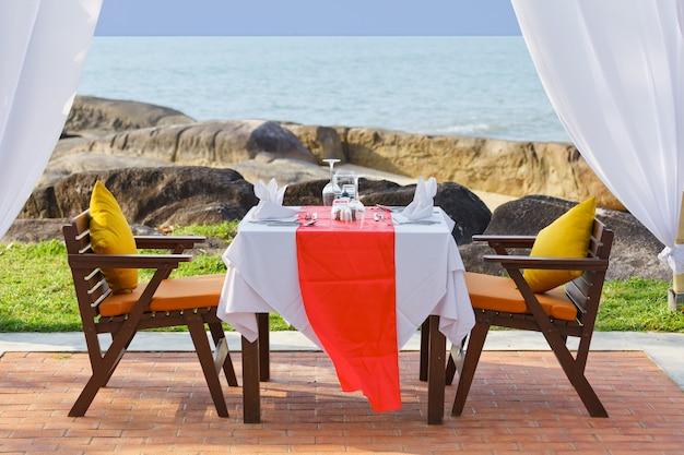 Tafel voor het diner naast het strand bij zonsondergang