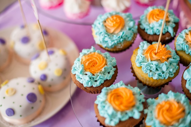 Tafel voor kinderen met cupcakes met blauwe en oranje top en decoritems in fel roze en blauw