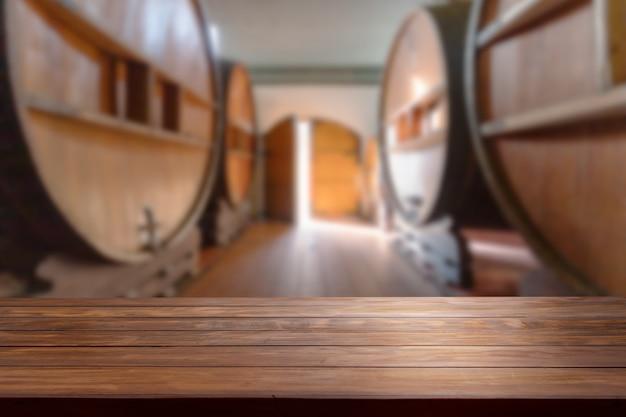Tafelblad in een wazige wijnkamer met grote wijnvaten door de hele kamer.