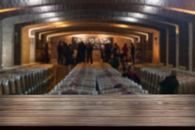 Tafelblad in een wazige wijnkamer met wijnvaten door de hele kamer.