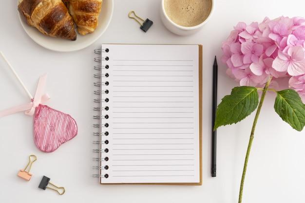 Tafelblad met open notitieboekje, kopje koffie, roze hortensia.