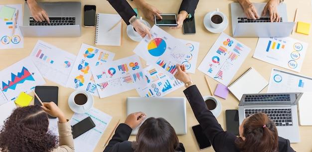 Tafelbladweergave van een houten vergadertafel met verschillende grafieken en grafiekpapieren erop en zes zakelijke vrouwenhanden die op tablet en laptop rond de tafel werken. concept voor zakelijke bijeenkomst.