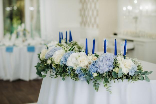 Tafeldecoratie bruiloft met blauwe bloemen op de tafel in het tafeldecor van het restaurant voor het diner op de bruiloft.