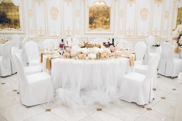 Tafeldecoratie bruiloft met bloemen op de tafel in het kasteel, tafeldecoratie voor het diner bij kaarslicht.