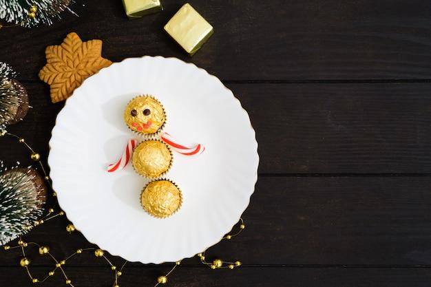 Tafeldecoratie van kerstmis met sneeuwpop van snoepjes op plaat met kerstboom