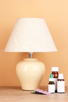 Tafellamp en medicijnen op beige oppervlak