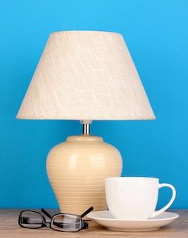 Tafellamp met kop en glazen op blauw