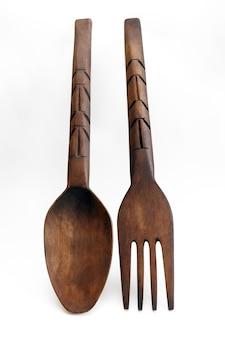 Tafellepel en vork van hout op wit wordt geïsoleerd