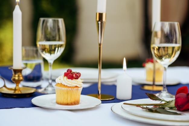 Tafelopstelling, glazen, kaarsen, bloemen en snoepjes op de platen close-up, niemand. luxe zilverwerk en wit tafelkleed, servies buitenshuis