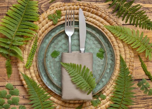 Tafelopstelling met varenbladeren op houten tafelblad. groene keramische platen met forn en mes. tropische platliggende scène