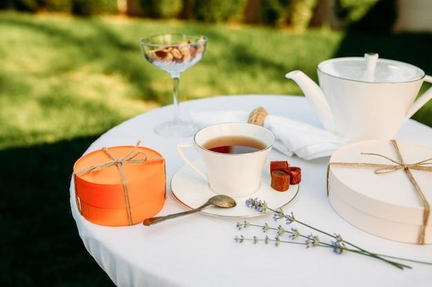 Tafelopstelling, romantisch theekransje met snoep, bovenaanzicht, niemand. luxe zilverwerk op wit tafelkleed, servies buitenshuis.