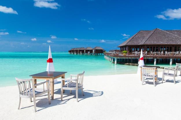Tafels en stoelen op het strand met uitzicht op zee. hotel in maldiven