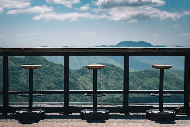 Tafels en stoelen op het terras met uitzicht op de bergen en de lucht. vintage toon