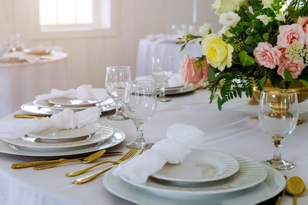 Tafels feestelijke set en bloemen voor een huwelijksreceptie