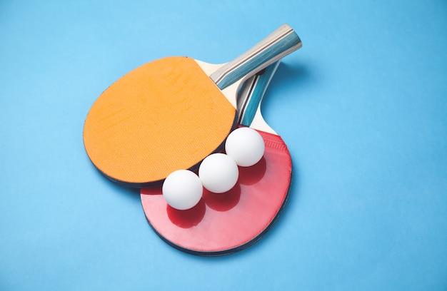 Tafeltennisrackets en witte plastic ballen op een blauwe achtergrond.