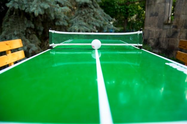 Tafeltennisspel en een bal op groen tennisbord