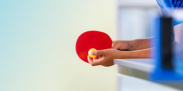 Tafeltennistafel, man tafeltennis spelen met racket en bal in een sporthal