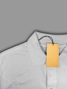 Tag prijs op wit poloshirt geïsoleerd op een grijze achtergrond