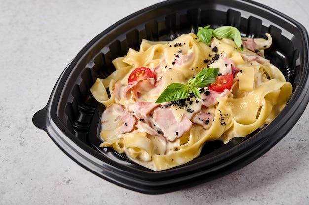 Tagliatelle carbonara in zwarte plastic container op lichte achtergrond close-up designer food concept