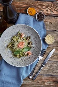 Tagliatelle met garnalen. huisgemaakte pasta met basilicumsaus en garnalen en parmizaanse kaas.