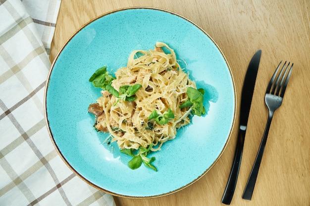 Tagliatelle met kip, witte saus en parmezaanse kaas in blauwe kom op houten tafel. traditionele huisgemaakte italiaanse pasta. detailopname