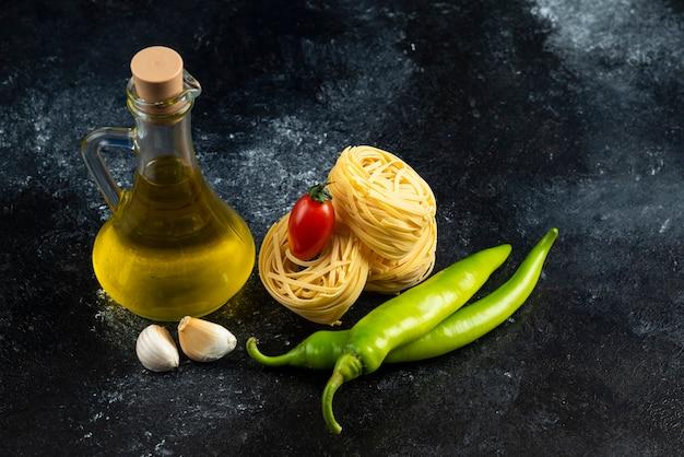 Tagliatelle nesten, olie en groenten op marmeren oppervlak.
