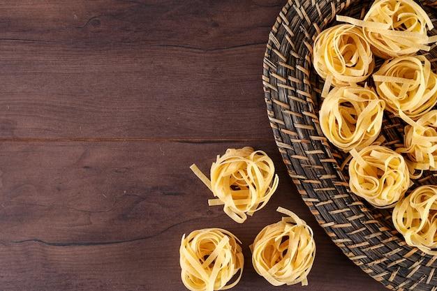 Tagliatelle pasta in mand bovenaanzicht met kopie ruimte op een houten oppervlak