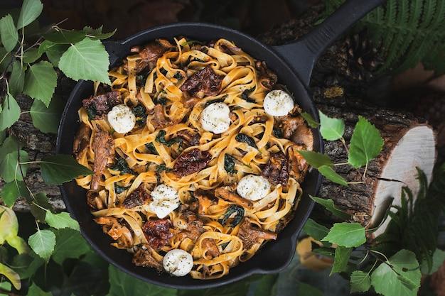 Tagliatelle-pasta met cantharellen, spinazie, zongedroogde tomaten en mozzarella