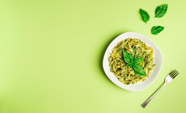 Tagliatelle pasta met pestosaus basilicum en pijnboompitten op lichtgroene achtergrondminimalistisch design