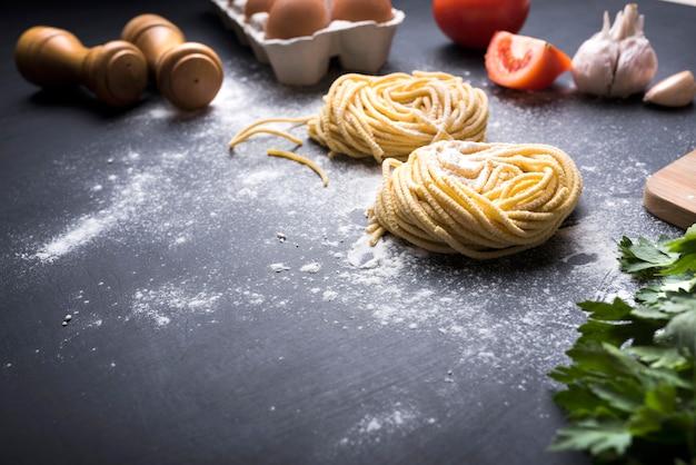 Tagliatelle pasta nest met ingrediënten en pepermolen boven aanrecht