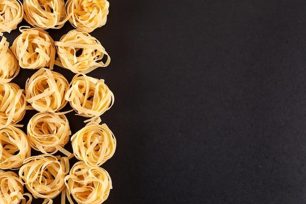 Tagliatelle pasta op het linker zwarte oppervlak bovenaanzicht met kopie ruimte