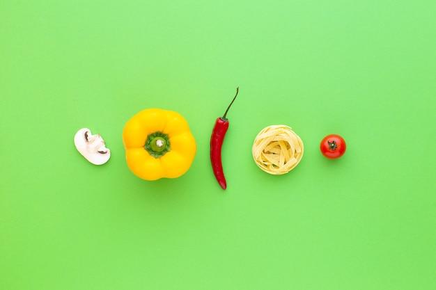 Tagliatelle rauwe pasta en groenten op groene achtergrond bovenaanzicht