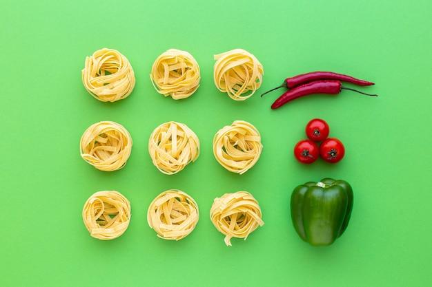 Tagliatelle rauwe pasta nesten en groenten op groene achtergrond bovenaanzicht