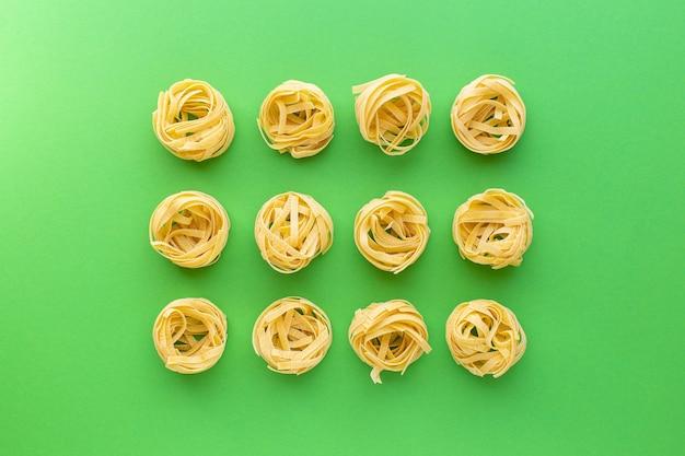 Tagliatelle rauwe pasta nesten op groene achtergrond bovenaanzicht