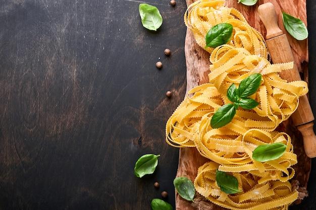 Tagliatelle. zelfgemaakte pasta, basilicumblaadjes, bloem, peper, olijfolie, cherrytomaat en deegroller en pastames op donkere oude houten achtergrond. voedselconcept. bespotten. horizontaal met kopie ruimte.