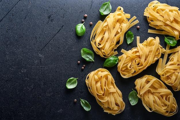 Tagliatelle. zelfgemaakte pasta, basilicumblaadjes, bloem, peper, olijfolie en cherrytomaat op donkere zwarte achtergrond. voedselconcept. bespotten. horizontaal met kopie ruimte.