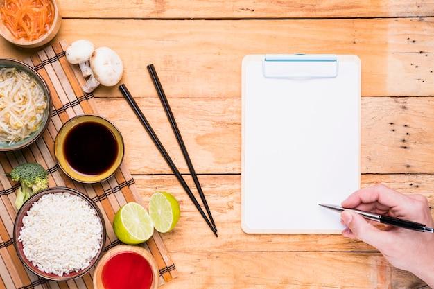 Tai-voedsel met de hand die van een persoon op het klembord met pen op houten bureau schrijven