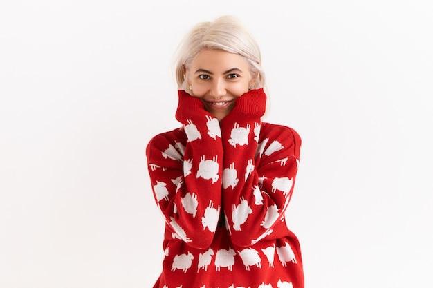 Taille afbeelding van aantrekkelijke charmante tienermeisje met geverfd haar mouwen van haar favoriete trui uitrekken. schattige jonge vrouw gekleed in trui met vriendelijke positieve gezichtsuitdrukking