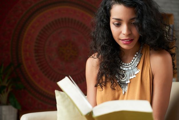 Taille die van aantrekkelijke latijnse vrouw is ontsproten die een boek leest
