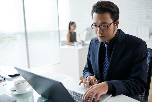 Taille die van aziatische zakenman is ontsproten die bij laptop in coworking ruimte werkt