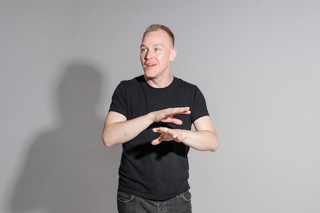 Taille foto van expressieve man in zwart shirt zijn handen kruisen tijdens het poseren in professionele studio