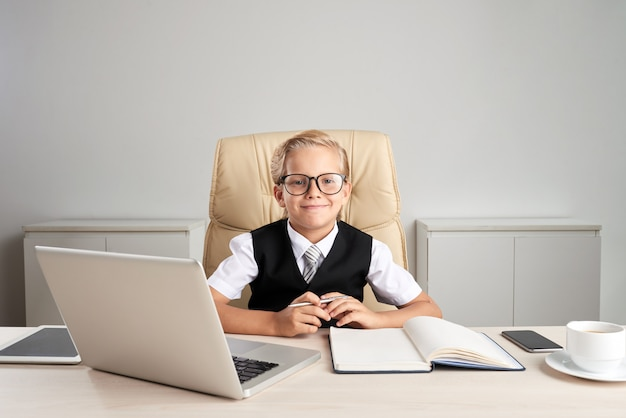 Taille omhoog geschoten van kleine blanke blonde jongen zittend aan het bureau in formalwear spelen van de grote baas