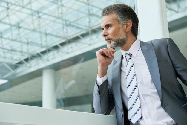 Taille omhoog geschoten van knappe man van middelbare leeftijd die pak en stropdas draagt en nadenkt over nieuwe ideeën