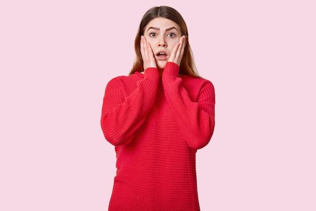 Taille omhoog geschoten van verbaasde jonge vrouw raakt wangen aan, gekleed in rode trui, drukt schok uit, poseert over rooskleurig