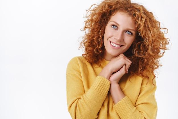 Taille-omhoog portret, mooie gekrulde roodharige vrouw in gele trui, aankleden voor feest in warme, gezellige outfit, handen ineen slaan en glimlachen, staren met genegenheid, tederheid en verrukking