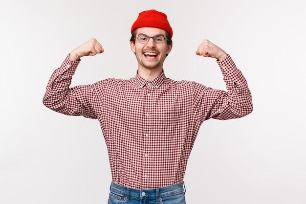 Taille-omhoog portret van aangemoedigde en energieke jonge zelfverzekerde slanke kerel in rode muts en glazen flex biceps, laat zijn spieren sterk en krachtig zien,