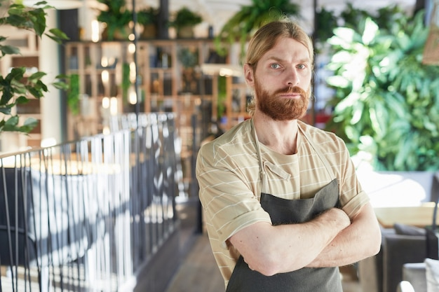 Taille omhoog portret van bebaarde cafémedewerker die schort draagt en naar de camera kijkt terwijl hij met gekruiste armen in een milieuvriendelijk groen interieur staat, kopieer ruimte