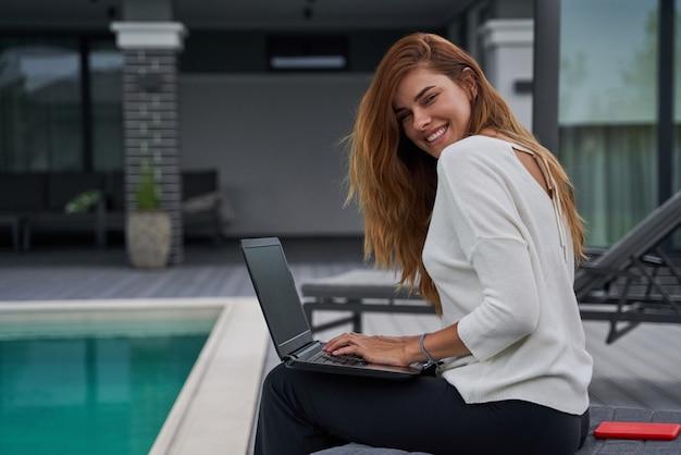 Taille omhoog portret van charmante jonge vrouw zittend aan de chaise longue met laptop en werken. ze kijkt naar de camera en lacht